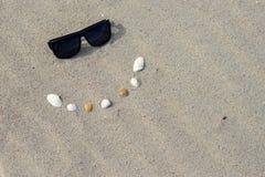 Τα γυαλιά ηλίου και τα κοχύλια δημιουργούν ένα χαμόγελο για να τιτιβίσουν Στοκ φωτογραφία με δικαίωμα ελεύθερης χρήσης