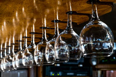 Τα γυαλιά κρασιού κρεμούν στο απόθεμα φραγμών Στοκ Εικόνες