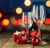 Τα γυαλιά κρυστάλλου με τα Χριστούγεννα ανάβουν το υπόβαθρο Μέρος Χριστουγέννων Στοκ Φωτογραφία
