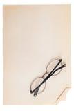 Τα γυαλιά που διπλώνονται βρίσκονται σε ένα εκλεκτής ποιότητας κομμάτι χαρτί Στοκ φωτογραφία με δικαίωμα ελεύθερης χρήσης