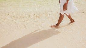 Τα γυμνά και μαυρισμένα πόδια μιας φιλιππινέζικης μαθήτριας σε ένα λευκό ντύνουν τον περίπατο στην άσπρη άμμο, σχετικά με τα foam στοκ φωτογραφία
