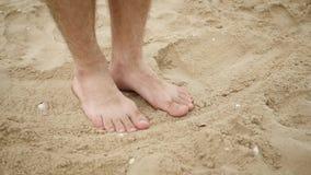 Τα γυμνά πόδια των ατόμων έρχονται στην άμμο θαλασσίως, αφήνοντας ένα ίχνος τουριστών απόθεμα βίντεο