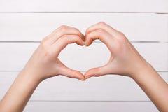 Τα γυναικεία δάχτυλα παρουσιάζουν σύμβολο καρδιών Αγάπη Στοκ Φωτογραφίες
