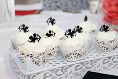 Τα γλυκά άσπρα cupcakes με τα μικρά cupids είναι στον πίνακα κατά τη διάρκεια του celeb Στοκ Φωτογραφία