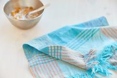 Τα δημητριακά σε ένα μέταλλο κυλούν με το γάλα σε ένα χρωματισμένο άσπρο ξύλινο υπόβαθρο Σύνθεση με μια πετσέτα και ένα κουτάλι π Στοκ εικόνα με δικαίωμα ελεύθερης χρήσης
