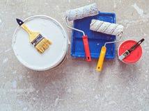 Τα διάφορα αντικείμενα για τη ζωγραφική λειτουργούν ένα δοχείο του χρώματος, βούρτσες, κύλινδροι, spatula βρίσκεται στο τσιμεντέν Στοκ Φωτογραφία