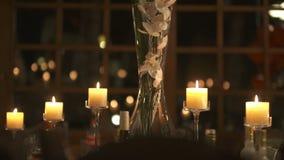 τα διακοσμημένα πέταλα μαργαριταριών εστίασης αυξήθηκαν ρηχός επιτραπέζιος γάμος Τόπος συναντήσεως δεξίωσης γάμου με τα αναμμένα  απόθεμα βίντεο