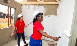 Τα διαφορετικά μέλη της κοινότητας προσχωρούν στο προσωπικό PWC ` s στην οικοδόμηση ενός χαμηλού μαρουλιού στοκ φωτογραφία με δικαίωμα ελεύθερης χρήσης