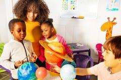 Τα διαφορετικά παιδάκια μαθαίνουν τους πλανήτες ηλιακών συστημάτων στοκ εικόνα με δικαίωμα ελεύθερης χρήσης