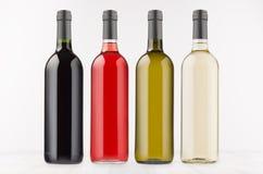 Τα διαφορετικά χρώματα συλλογής μπουκαλιών κρασιού στο λευκό ξύλινο πίνακα, χλευάζουν επάνω Πρότυπο για τη διαφήμιση, σχέδιο, ταυ στοκ εικόνες