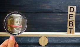 """Τα δολάρια και η επιγραφή """"χρέος """"είναι στις κλίμακες Έννοια της οικονομικής κρίσης και των προβλημάτων Έννοια διαχείρησης κινδύν στοκ εικόνα"""