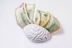 Τα δολάρια χρημάτων είναι μεταξύ των ημισφαιρίων του ανθρώπινου εγκεφάλου Η φωτογραφία έννοιας, συμβολισμός υψηλός πληρώνει της δ στοκ φωτογραφίες