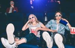 Τα δροσερά και χαλαρωμένα κορίτσια κάθονται στον κινηματογράφο πρώτων γραμμών και προσοχής Έχουν βάλει τα πόδια τους επάνω Επίσης Στοκ φωτογραφία με δικαίωμα ελεύθερης χρήσης
