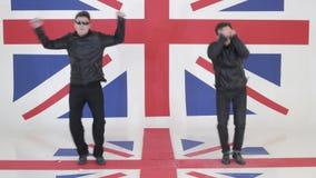 Τα δυναμικά άτομα με τα γυαλιά ηλίου και τα μαύρα σακάκια μοτοσικλετών δέρματος χορεύουν απόθεμα βίντεο