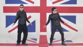 Τα δυναμικά αρσενικά με τα γυαλιά ηλίου και τα μαύρα σακάκια μοτοσικλετών δέρματος χορεύουν απόθεμα βίντεο