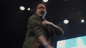 Τα δυναμικά κορίτσια στα σκούρο πράσινο κοστούμια με τα χρωματισμένα πρόσωπα χορεύουν συγχρονικά απόθεμα βίντεο