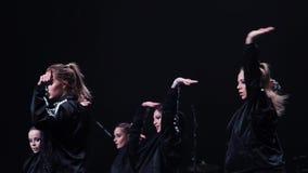 Τα δυναμικά χαριτωμένα κορίτσια στα μαύρα αθλητικά μαύρα ενδύματα χορεύουν στη σκηνή στο φεστιβάλ απόθεμα βίντεο