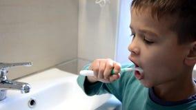 Τα δόντια βουρτσίσματος αγοριών παιδιών και εξέταση τον καθρέφτη, δραστηριότητες πρωινού, πλένουν τα χέρια του απόθεμα βίντεο