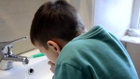 Τα δόντια βουρτσίσματος αγοριών παιδιών και εξέταση τον καθρέφτη, δραστηριότητες πρωινού, πλένουν τα χέρια του φιλμ μικρού μήκους