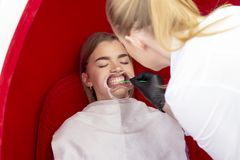 Τα δόντια που λευκαίνουν τον οδοντίατρο υποδοχής κοριτσιών διαδικασίας για τα δόντια που λευκαίνουν το γιατρό εφαρμόζουν το φάρμα στοκ εικόνα