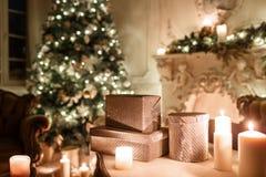 Τα δώρα στον πίνακα Βράδυ Χριστουγέννων από το φως ιστιοφόρου κλασικά διαμερίσματα με μια άσπρη εστία, διακοσμημένο δέντρο Στοκ Εικόνες
