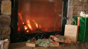 Τα δώρα Χριστουγέννων που διακοσμούνται με τους κομψούς κλάδους, κώνοι, κορδέλλες βάζουν από την εστία Θερμό κάψιμο πυρκαγιάς κού φιλμ μικρού μήκους