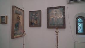 Τα εικονίδια στον τοίχο στη Ορθόδοξη Εκκλησία και τα κεριά είναι κοντινά Πανόραμα απόθεμα βίντεο