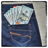 Τα εκλεκτής ποιότητας αμερικανικά χρήματα grunge είναι στην τσέπη του τζιν παντελόνι Στοκ Φωτογραφία