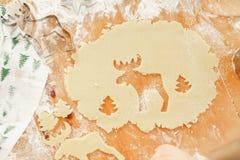 Τα ελάφια και το νέο δέντρο έτους που κόβονται στη ζύμη, έτοιμα μπισκότα των διαφορετικών μορφών βρίσκονται στον ξύλινο πίνακα, π Στοκ φωτογραφίες με δικαίωμα ελεύθερης χρήσης