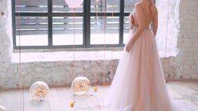 Τα ελαφριά φωτεινά μπαλόνια βρίσκονται και κυλούν στο πάτωμα, που γεμίζουν με χρυσό serpentine, ακτινοβολούν λαμβάνοντας υπόψη το φιλμ μικρού μήκους
