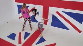 Τα ελκυστικά θηλυκά στα σύγχρονα ενδύματα χορεύουν χαρωπά στη βρετανική σημαία απόθεμα βίντεο