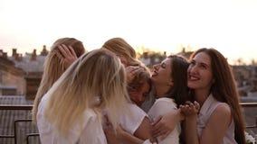 Τα ελκυστικά καυκάσια κορίτσια αγκαλιάζουν να σταθούν έξω σε ένα πεζούλι ή ένα μπαλκόνι Έξι όμορφες νέες γυναίκες στο λευκό απόθεμα βίντεο