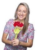 τα ελκυστικά λουλούδια δίνουν τη χαμογελώντας γυναίκα της Στοκ Εικόνες