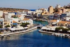 Τα ελληνικά κτήρια παράδοσης, λιμάνι, λίμνη Voulismeni που συνδέεται με τη Μεσόγειο βλέπουν στο κέντρο της παραλιακής πόλης Άγιος Στοκ εικόνα με δικαίωμα ελεύθερης χρήσης