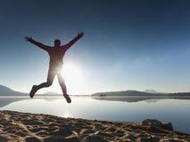 Τα ενήλικα τρελλά άλματα ατόμων ποτίζουν πλησίον επάνω ενάντια στο κόκκινο ηλιοβασίλεμα παραλία κενή Στοκ Φωτογραφίες