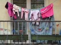 Τα ενδύματα των παιδιών είναι ξηρά σε ένα σχοινί στο μπαλκόνι: ρόδινες φόρμες, αθλητικές κιλότες, κάλυμμα για να δημιουργήσει ένα Στοκ φωτογραφία με δικαίωμα ελεύθερης χρήσης