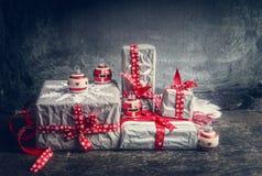 Τα εορταστικά δώρα και παρουσιάζουν τη διακόσμηση με χειροποίητα snowflakes εγγράφου περικοπών και τις κόκκινες κορδέλλες Στοκ Φωτογραφίες