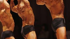 Τα επαγγελματικά αρσενικά bodybuilders που καταδεικνύουν τους σχισμένους lat μυς στο οπίσθιο τμήμα θέτουν φιλμ μικρού μήκους