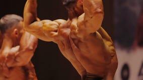 Τα επαγγελματικά αρσενικά bodybuilders που παρουσιάζουν τεράστιους μυς στους πίσω διπλούς δικέφαλους μυς θέτουν απόθεμα βίντεο