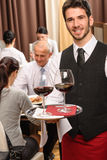 τα επιχειρησιακά γυαλιά κρατούν το κρασί σερβιτόρων εστιατορίων μεσημεριανού γεύματος Στοκ φωτογραφία με δικαίωμα ελεύθερης χρήσης