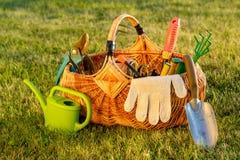 Τα εργαλεία κηπουρικής στο καλάθι και πότισμα μπορούν στη χλόη Στοκ φωτογραφίες με δικαίωμα ελεύθερης χρήσης