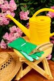 Τα εργαλεία κηπουρικής στον ξύλινο πίνακα και αυξήθηκαν υπόβαθρο λουλουδιών Στοκ εικόνα με δικαίωμα ελεύθερης χρήσης
