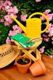 Τα εργαλεία κηπουρικής στον ξύλινο πίνακα και αυξήθηκαν υπόβαθρο λουλουδιών Στοκ Εικόνες