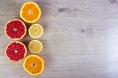 Τα εσπεριδοειδή κόβουν τα πορτοκάλια υποβάθρου, λεμόνια, γκρέιπφρουτ σε ένα φωτεινό ξύλινο υπόβαθρο Στοκ Εικόνες