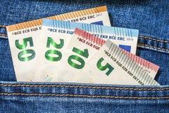 Τα ευρο- τραπεζογραμμάτια χρημάτων σε μια τσέπη του τζιν παντελόνι κλείνουν επάνω στοκ φωτογραφία
