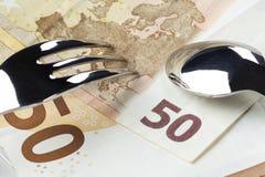 Τα ευρώ τραπεζογραμματίων 50 και 10 είναι σε ένα άσπρο πιάτο με μπλε σύνορα Πάνω από τους είναι ένα δίκρανο και ένα κουτάλι στοκ φωτογραφίες