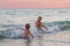 Τα ευτυχή αγόρια παίζουν στα κύματα στην παραλία Τα εύθυμα αγόρια λούζουν στα κύματα θάλασσας στο ηλιοβασίλεμα στοκ εικόνα με δικαίωμα ελεύθερης χρήσης