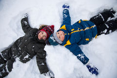 Τα ευτυχή αγόρια στο χιόνι παίζουν και χαμογελούν την ηλιόλουστη ημέρα Στοκ φωτογραφία με δικαίωμα ελεύθερης χρήσης
