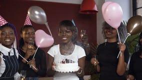 Τα ευτυχή ελκυστικά αφρικανικά φυσώντας κεριά κοριτσιών στο κέικ γενεθλίων περιέβαλαν τους φίλους της απόθεμα βίντεο