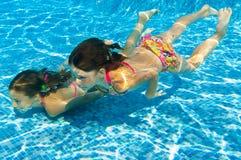 Τα ευτυχή ενεργά υποβρύχια παιδιά κολυμπούν στη λίμνη στοκ εικόνες